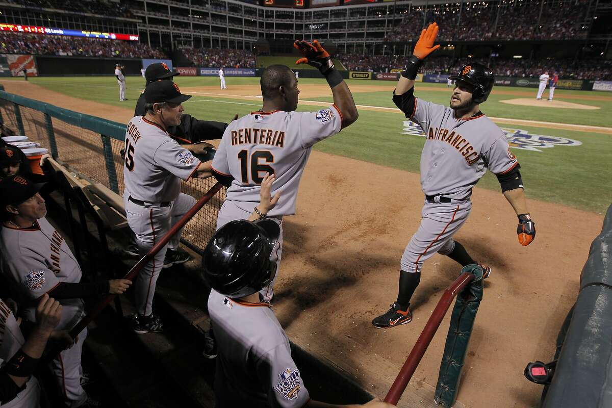 San Francisco Giants shortstop Edgar Renteria (16) greets San Francisco Giants center fielder Cody Ross (13) after Ross hit a solo homer in the seventh inning during game 3 of the 2010 World Series between the San Francisco Giants and the Texas Rangers on Saturday, Oct. 30, 2010 in Arlington, Tx.