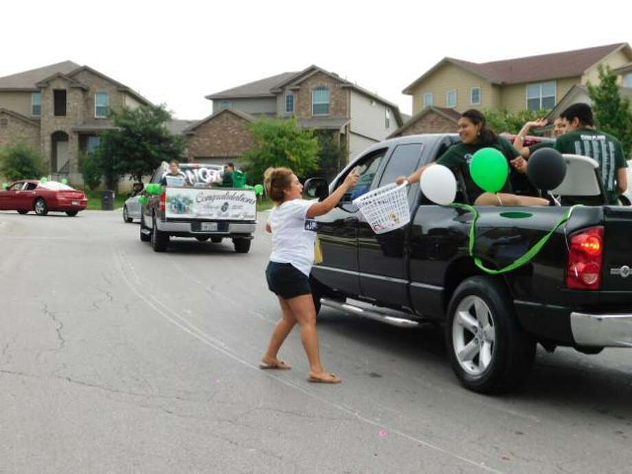 Amanda Lopez, a resident of the Solana Ridge subdivision, throws a snack item into the gift basket of a high school senior during a parade honoring graduates that took place in the subdivision on Sunday. Approximately 100 graduating seniors and their families participated in the parade. Most of the students who participated attended Southwest High School, but seniors from Southwest Legacy, Harlandale, and Brooks Academy who live in nearby neighborhoods also participated. Photo: Photos By David DeKunder /Staff
