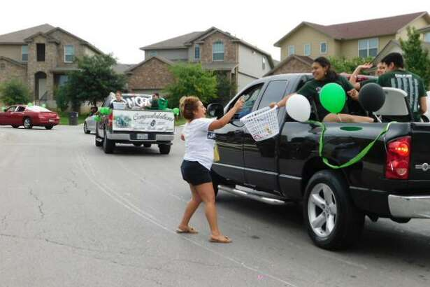 Amanda Lopez, a resident of the Solana Ridge subdivision, throws a snack item into the gift basket of a high school senior during a parade honoring graduates that took place in the subdivision on Sunday. Approximately 100 graduating seniors and their families participated in the parade. Most of the students who participated attended Southwest High School, but seniors from Southwest Legacy, Harlandale, and Brooks Academy who live in nearby neighborhoods also participated.