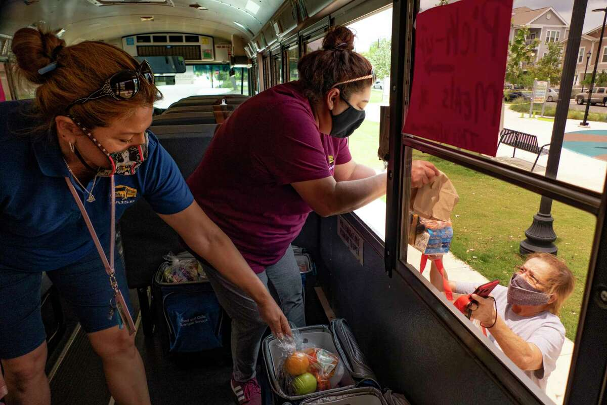 """Lupita Holguin, left, and Angie Salinas hand out lunch to people out of their SAISD """"Eats Bus"""" in June. SAISD, like many other districts, has continue to distribute food to families through the summer. Many of these families may not know they are eligible for an additonal $285 in food assistance."""