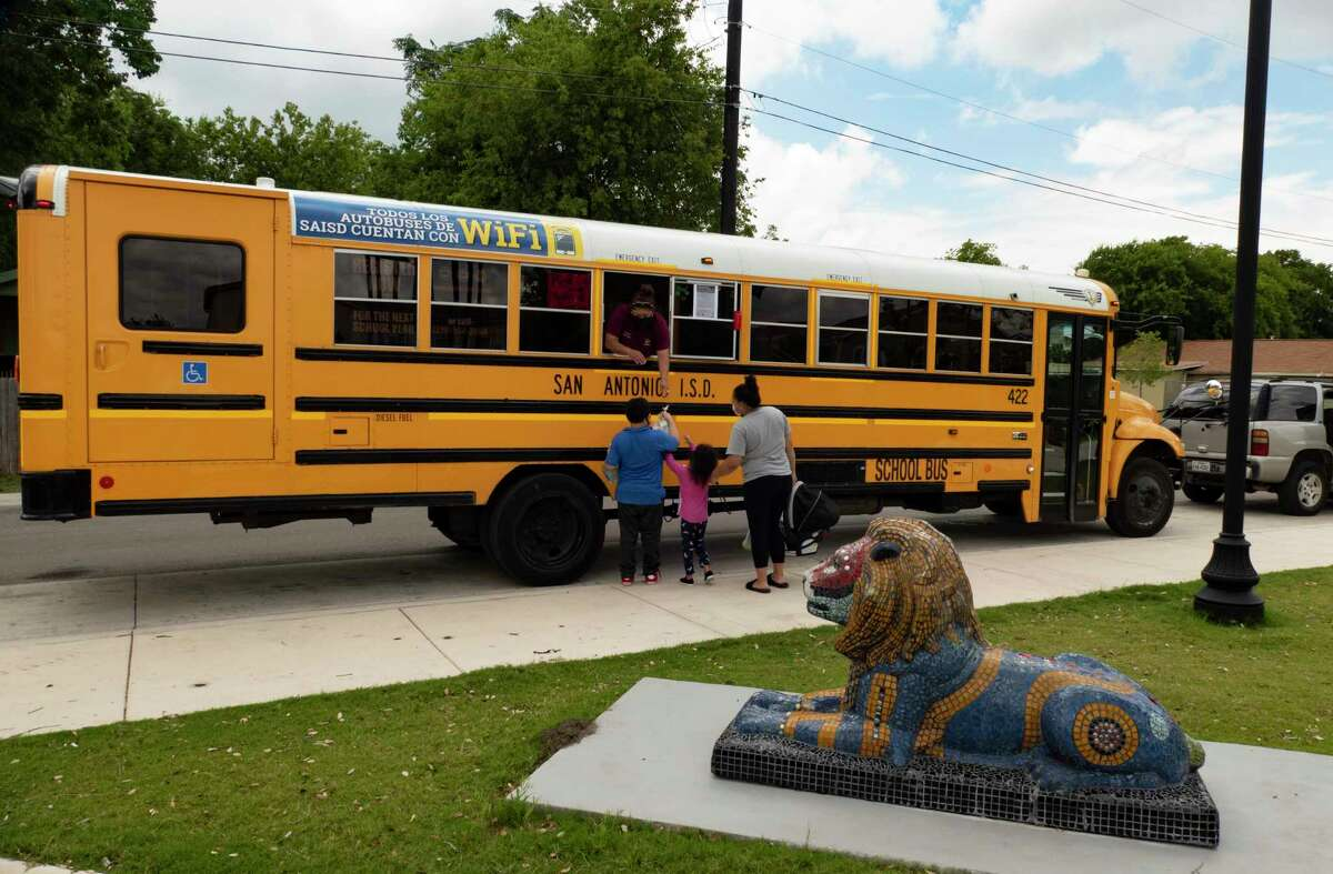 """Angie Salinas hands out lunch to people from the SAISD """"Eats Bus"""" at the East Meadows Apartments on Tuesday. School districts will continue to provide meals during the summer, some on modified schedules."""
