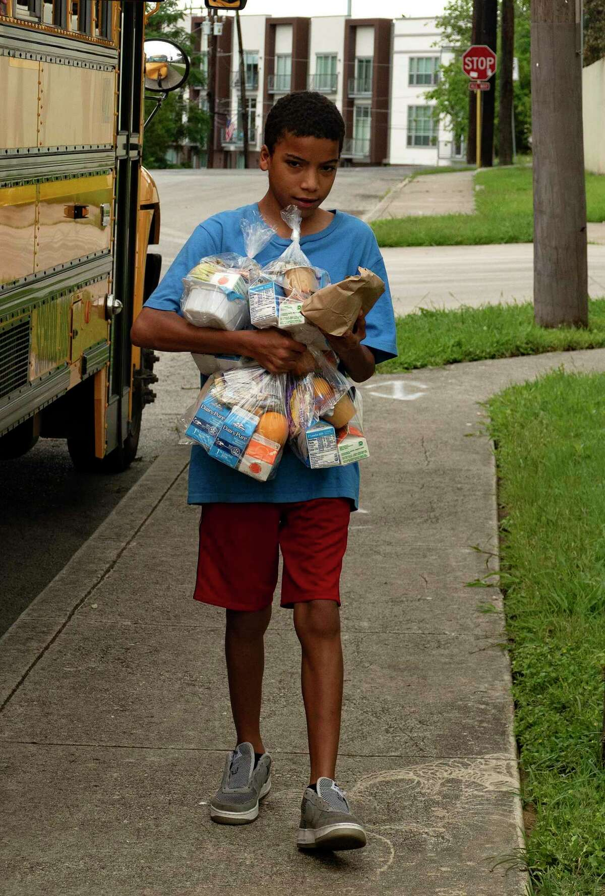 In June, a student carries food provided by SAISD. Families of Texas students who qualified for free or reduced price meals are eligible for $285 per student from the state. The deadline to apply is July 31.