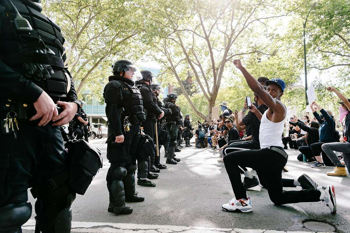 Kenroy Higgins of Oakland and other protestors take a knee and hold up their fists in front of a line of police officers in riot gear blocking North Broadway near the Walnut Creek Police Station as protestors gather for a George Floyd Solidarity Demonstration at nearby Civic Park in Walnut Creek, Calif, on Monday, June 1, 2020.