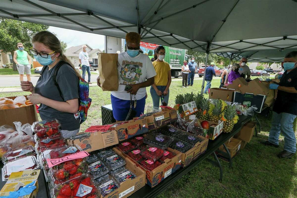 Skyler Cox, from left, and Cheryl Barrett shop for fruits and vegetables at the inaugural Fields of Dover Neighborhood Produce Market at 6239 Ironmill Creek on Friday. The two-hour extravaganza of fresh fruits and vegetables, was held for residents of the subdivision outside of Converse.
