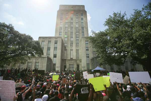 People hold up signs in front of Houston City Hall as they join George Floyd's family in a march on Tuesday, June 2, 2020.