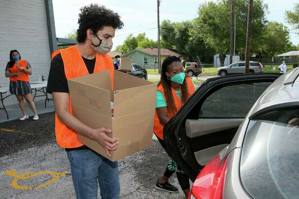 Francisco Torres, front left, and Kquintara Moses load a box of food into a recipient's car Saturday as the Fountain of Praise Church in Converse handed out 100 boxes of free food to needy families.