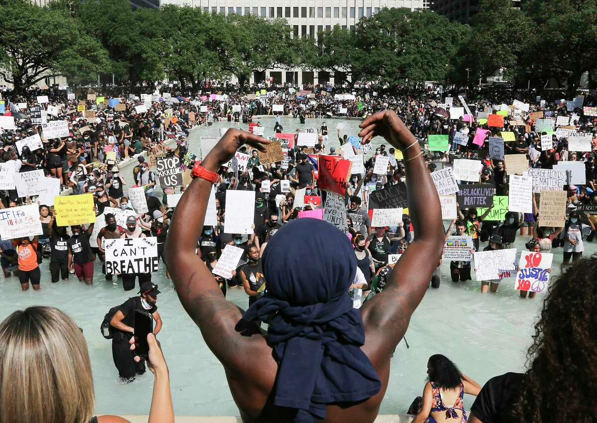 Protesters hold signs in the reflecting pool in front of Houston's City Hall as they listen to speeches after a march in honor of George Floyd on Tuesday, June 2, 2020.