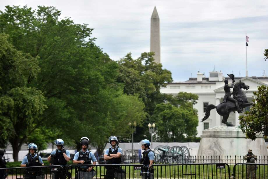Authorities stand guard behind a large fence as dozens of protesters rally outside of Lafayete Square in Washington, D.C., on Tuesday. Photo: Washington Post Photo By Marvin Joseph / The Washington Post