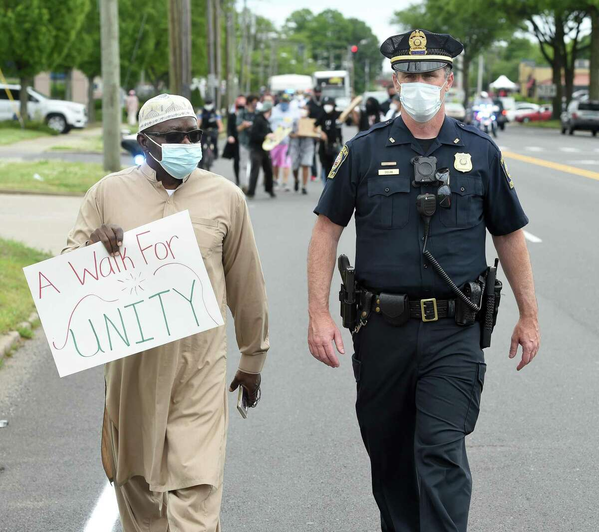 Caleb Rashids (left) of Hamden walks with Hamden Police Detective Sean Dolan (right) in a unity march up Dixwell Avenue in Hamden on June 2, 2020 in the aftermath of the George Floyd death at the hands of Minneapolis Police.