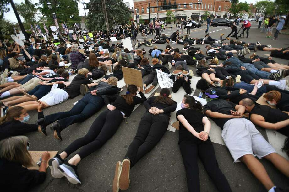 Protestors lie face down with hands behind their backs in the middle of the Post Road during an organized Black Lives Matter police brutality protest in Fairfield, Conn. on Tuesday, June 2, 2020. Photo: Brian A. Pounds / Hearst Connecticut Media / Connecticut Post