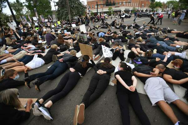 Protestors lie face down with hands behind their backs in the middle of the Post Road during an organized Black Lives Matter police brutality protest in Fairfield, Conn. on Tuesday, June 2, 2020.