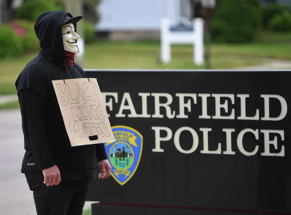 A Black Lives Matter protestor stands a solitary vigil outside the Fairfield Police Station during the protest in Fairfield, Conn. on Tuesday, June 2, 2020.