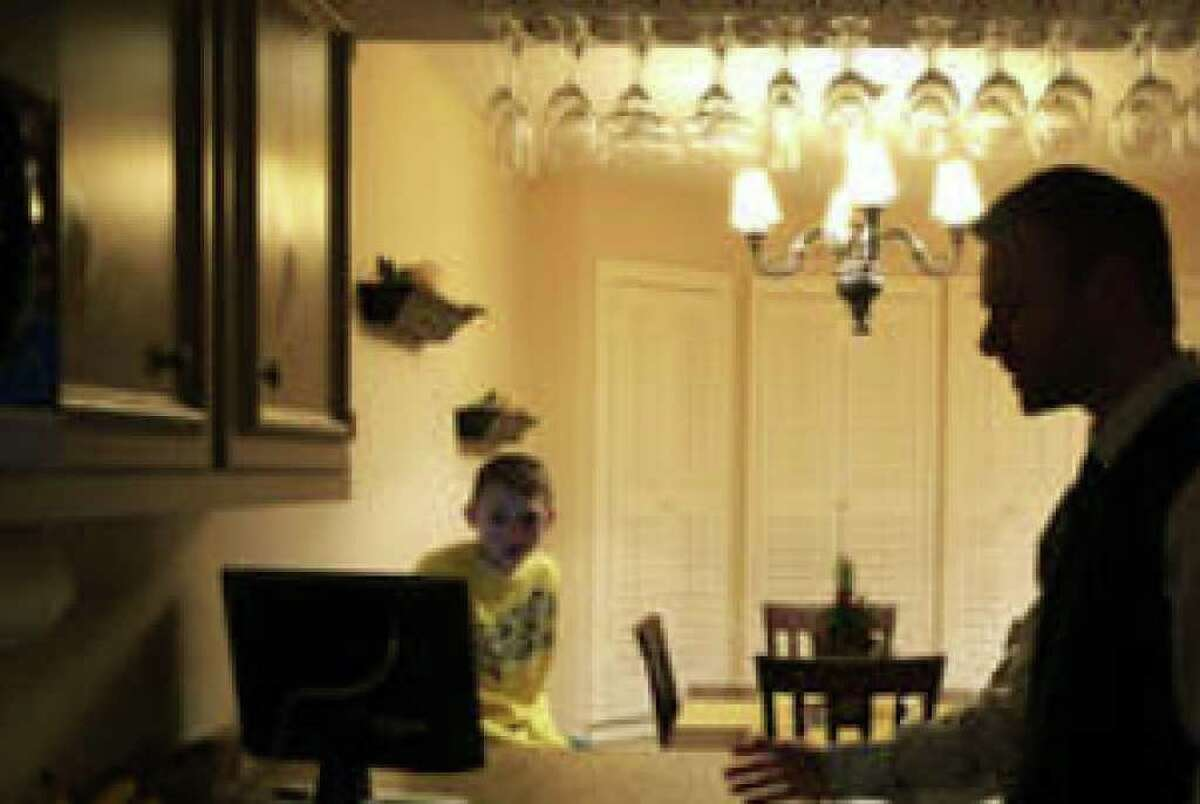 Child Advocates San Antonio volunteer Kevin Terrill talks with his son, Trevor, 13, at their apartment Wednesday. Terrill adopted Trevor years after working with him through CASA.