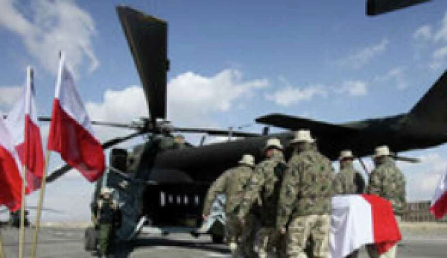 Polish soldiers carry the flag-draped casket of Pvt. 1 Michal Kolek, 22, into a Mil Mi-17 helicopter during a ceremony at Forward Operating Base Ghazni in Afghanistan. Around 150 Texas Army National Guard troops also took part in the ceremony.