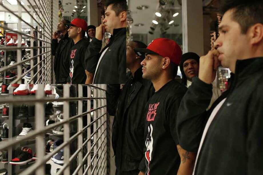 Customers Martin Kendall, Mando Cortez, Michael Mangrum and Fidel Paiz wait to buy Michael Jordan's Air Jordan XI Retro shoe outside Foot Locker in the Rivercenter Mall.