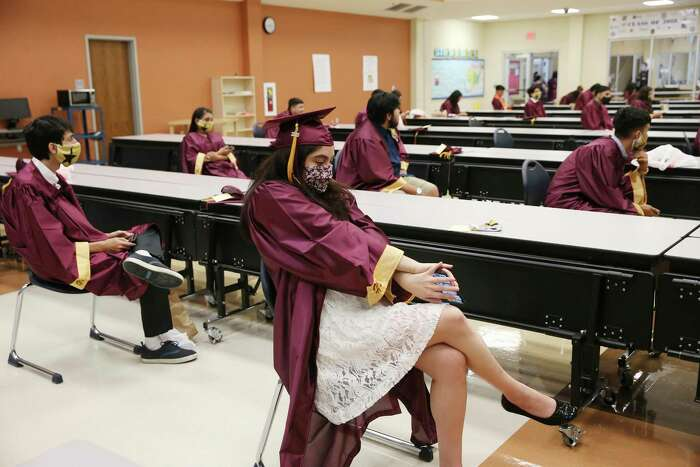 Crystal Valadez, 18, stretches as she and other seniors wait for the start of the Harlandale High School Commencement Ceremony at Harlandale Memorial Stadium, Tuesday, June 2, 2020. Precautions were taken by the Harlandale ISD due to the coronavirus. There were 400 students that participate in the ceremony with limited seats available for families.