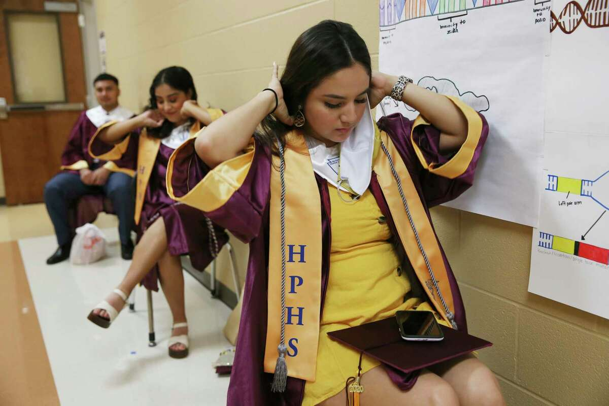 Alyson Rendon, 18, puts on her honor cord as she and other seniors wait for the start of the Harlandale High School Commencement Ceremony at Harlandale Memorial Stadium, Tuesday, June 2, 2020. Precautions were taken by the Harlandale ISD due to the coronavirus. There were 400 students that participate in the ceremony with limited seats available for families. She is will be attending the University of Texas at Austin.
