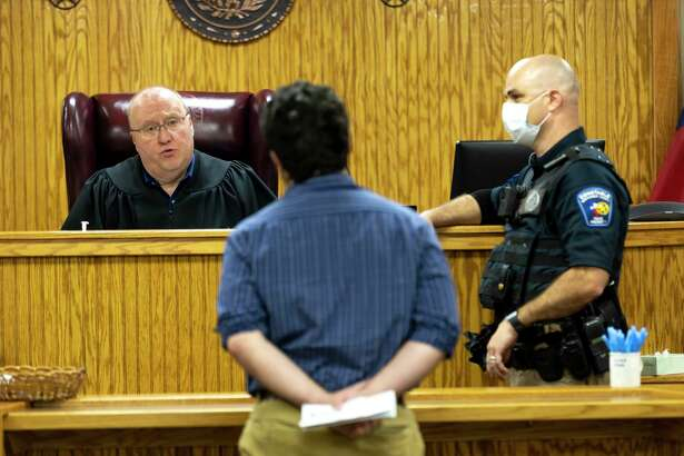 Precinct 1 Judge Wayne Mack, left, a defendant and deputy Paul Bostick practice social distancing during a docket hearing at the Montgomery County Justice of Peace Precinct 1 court building in Willis, Tuesday, June 2, 2020. New safety guidelines were put in place to stop the spread of COVID-19.