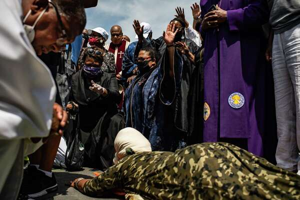 """Twin Cities clergy members pray Tuesday at a memorial for George Floyd in Minneapolis. As unrest tied to Floyd's killing while in police custody has spread to other parts of the country, including Washington, a relative calm has emerged in Minneapolis, even as protests continue. """"We have really seen the temperature change,"""" said John Harrington, commissioner of the state Department of Public Safety."""