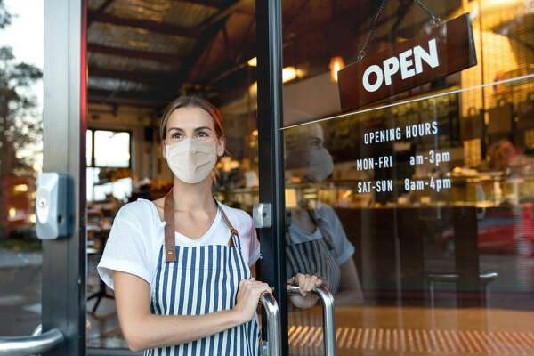"""Happy business owner opening the door at a cafe wearing a facemask to avoid the spread of coronavirus â€Â?"""" reopening after COVID-19 concepts"""
