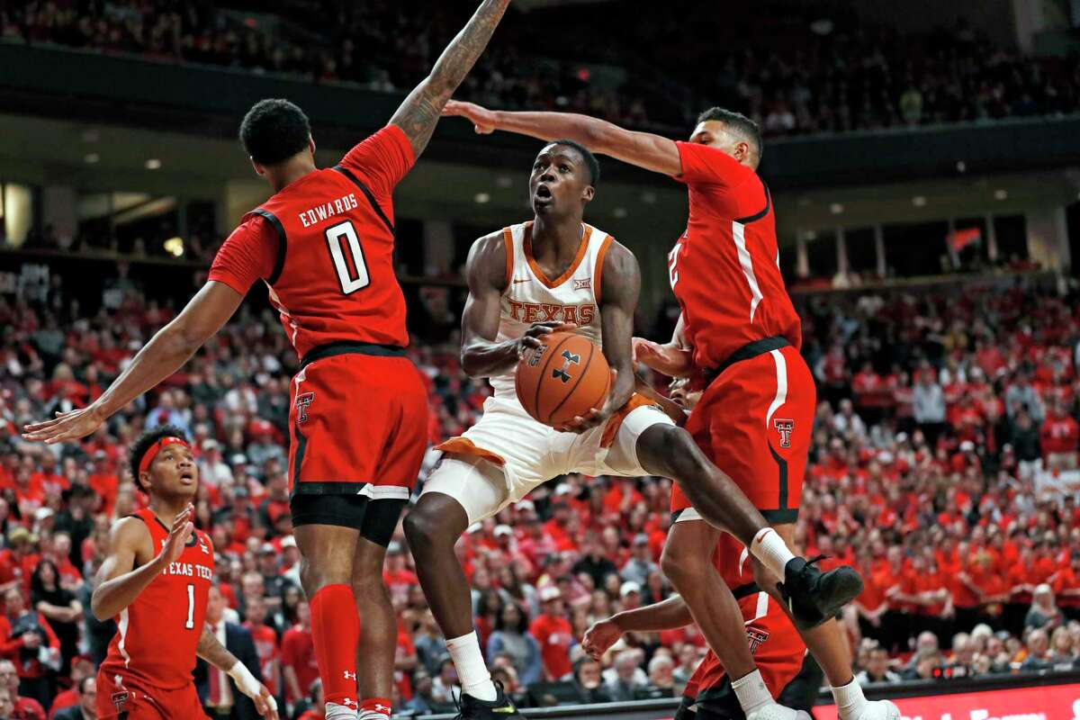 Texas' Andrew Jones (1) lays the ball up between Texas Tech's Kyler Edwards (0) and TJ Holyfield (22) during the first half of on Feb. 29, 2020, in Lubbock.