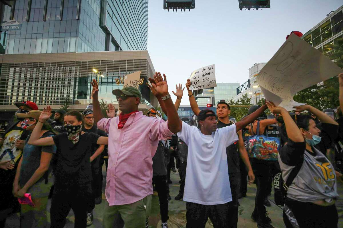 Men try to keep demonstrators from throwing anything during continued marching June 2, 2020, in downtown Houston during the fifth night of protests across the nation sparked by the death of former Houston resident George Floyd.
