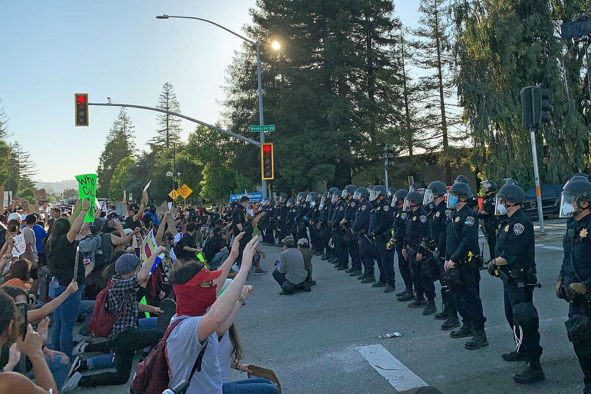 Marchers faced cops who were blocking the Woodside road ramp to highway 101 in Redwood City, Calif. on Tuesday, June 2, 2020. The marchers knelt and chanted for the cops to take a knee.