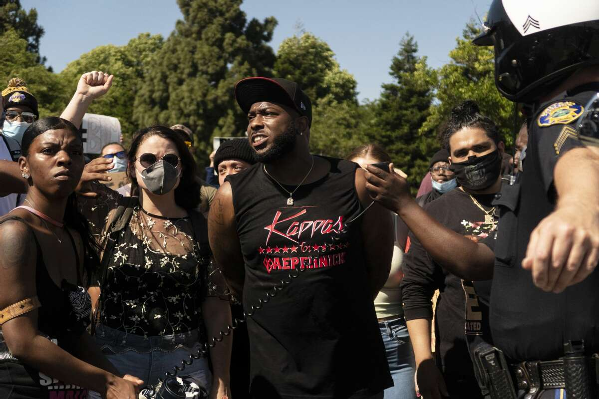 Brandon Coleman, center, talks to a crowd and Vallejo police officer Shane Bowers during a demonstration in Vallejo.