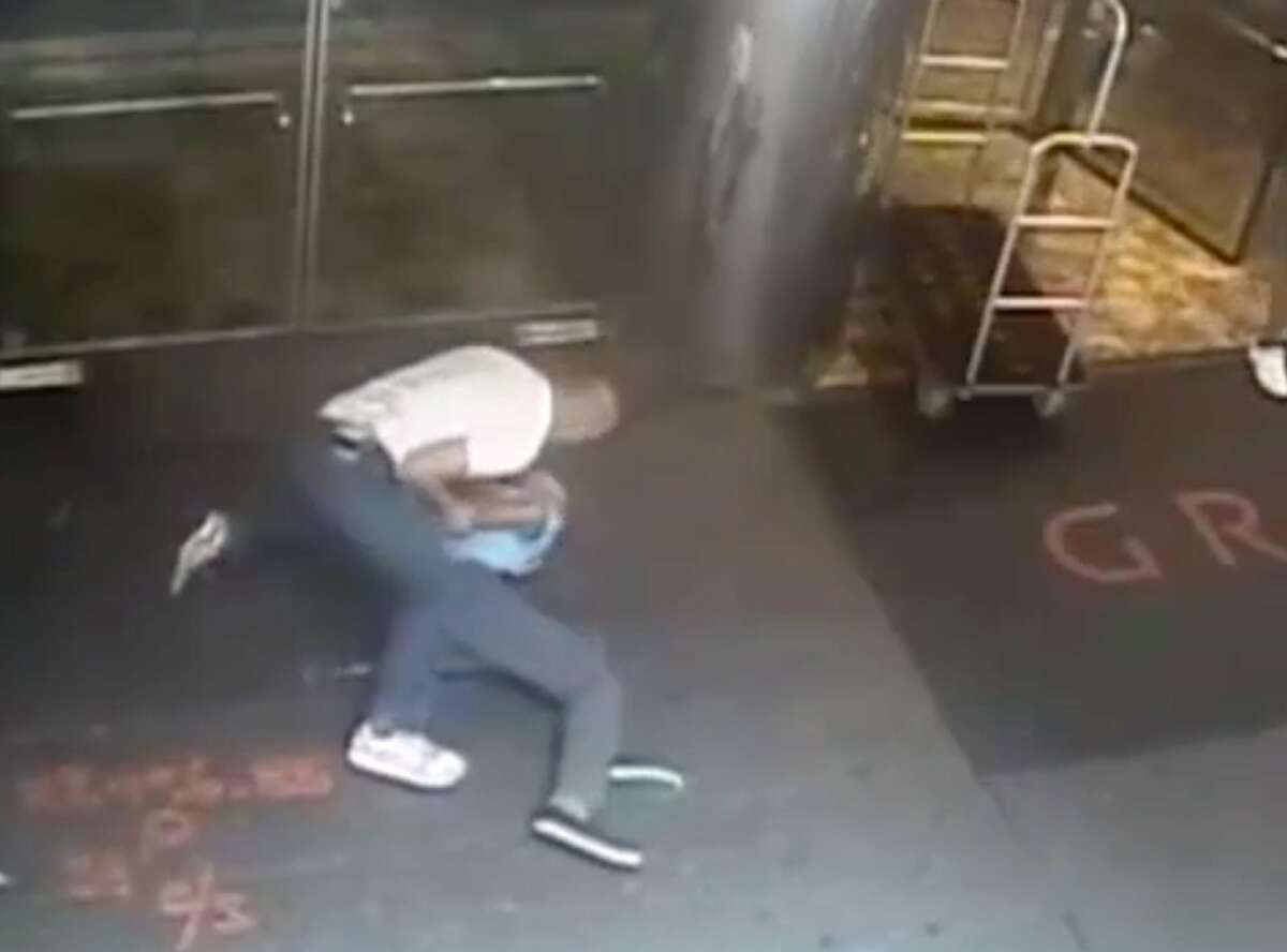 """This image taken from a surveillance camera and released by the New York Police Department shows former tennis star James Blake, right, being arrested by plainclothes officer James Frascatore outside of the Grand Hyatt New York hotel on Wednesday, Sept. 9, 2015, in New York. Blake was mistaken for an identity-theft suspect that Police Commissioner William Bratton said looked like Blake's """"twin."""" Bratton apologized to Blake. (NYPD via AP)"""