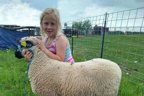 Brooklynn Rowe with her market lamb, Bubba. She's part of The Barnyard Bunch.