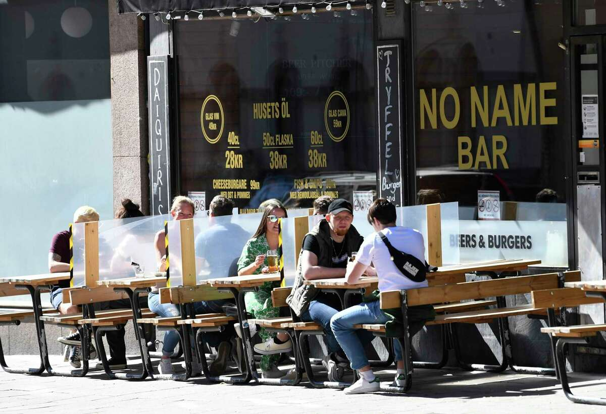 Screens between the tables protect customers sitting outside at a restaurant in central Stockholm Saturday May 30, 2020, during the coronavirus pandemic. Social distancing is an issue as warm wether has drawn crowds to many parks in the capital. (Henrik Montgomery / TT via AP)