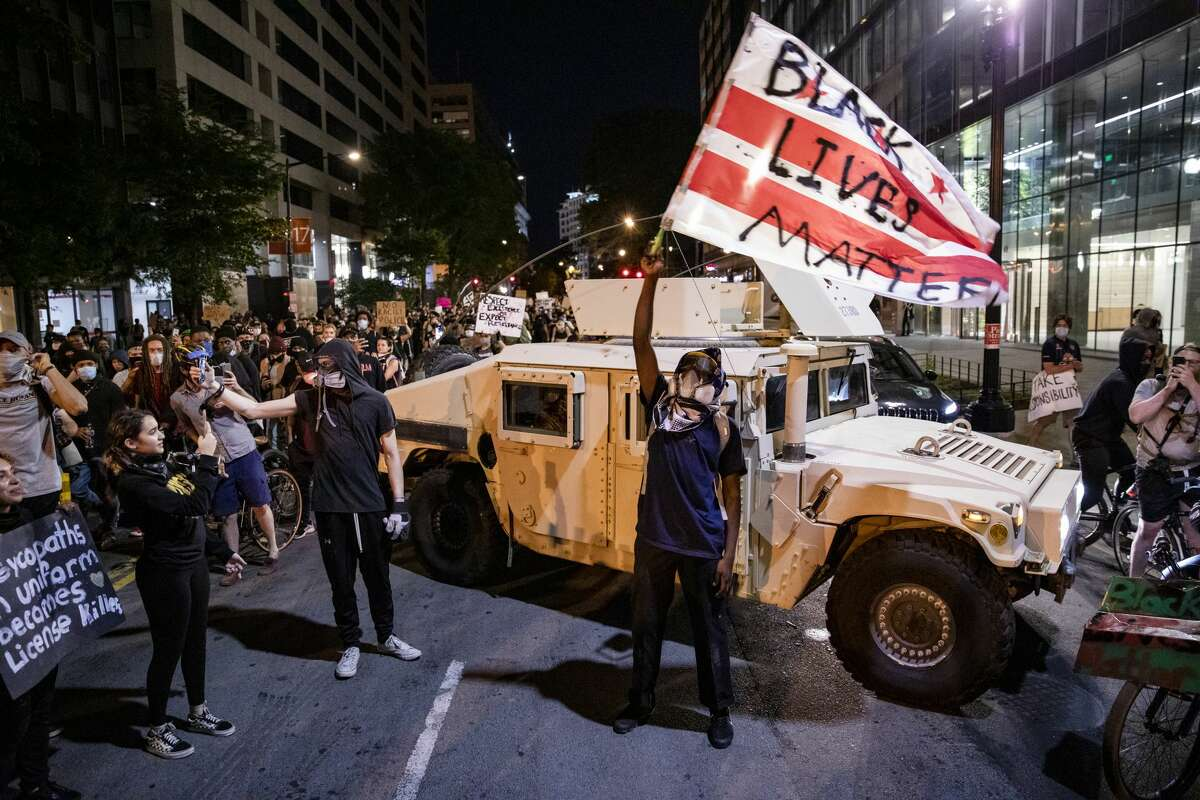 A protestor waves a DC flag with Black Lives Matter spray painted on it next to a DC National Guard Humvee as protestors march through the streets during a demonstration over the death of George Floyd, who died in police custody, on June 2, 2020 in Washington, DC. Protests erupted around the country following the release of a video showing Derek Chauvin, a now former Minneapolis Police officer, kneeling on the neck of Floyd despite Floyd saying I cant breath. (Photo by Samuel Corum/Getty Images)