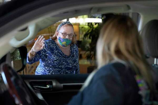 Ruth Steinfeld waves to her granddaughter, Jennifer Beleiff, and great-granddaughters, Madison, 5, and Avery, 2, as they sit in their vehicle during a quick drive by visit outside her residence amid the Covid-19 pandemic Wednesday, April 29, 2020, in Houston. The 87-year-old widower, great-grandmother of 7 and grandmother of 5, has lived in Houston since 1948 when she came to the U.S. after the Holocaust. She said she knows the toll of isolation on humans. But she has hope that this won't last long, there's a light at the end of the tunnel.