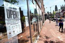 An OPEN sign hangs in the window of Urban Outfitters on Broadway in New Haven on the first day of the phased reopening of businesses in Connecticut on May 20, 2020.