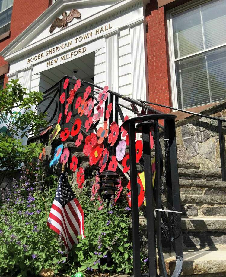 Poppies made by members of the Charles Merriman Society, Children of the American Revolution and New Milford residents adorn the front of Roger Sherman Town Hall in New Milford, as well as around the war memorials and gardens on the Village Green, in recognition of Memorial Day. Photo: Deborah Rose /Hearst Connecticut Media / Danbury News Times