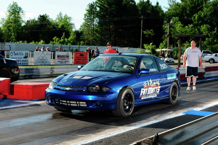 "Melissa Taylor of Hemlock scored a Street Trophy win in this Chevy Cavalier, sponsored by Fatt Matt's Barbecue in Munger.  The ""Lil' Blue"" entry, competes in all 4 divisions at NMD. Ben Wenzel Jr, looking on behind her, has the entry in among a 5-way tie for 11th place in Bracket II standings. (Submitted photo/Chris Simmons Photography) / Chris Simmons Photography"
