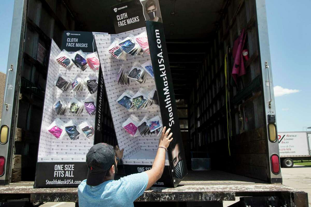 Rais Thobhani loads a face mask display into a truck at Ionized LLC, a Sugar Land glow stick manufacturer that is now importing PPE from China for Harris County, on Tuesday, May 26, 2020 in Sugar Land.