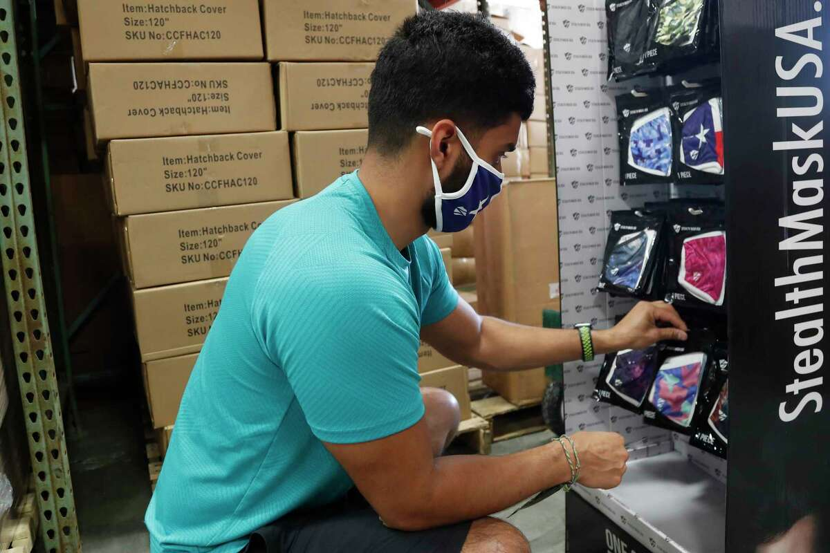 Khalil Maknojia organizes a mask display at Ionized LLC, a Sugar Land glow stick manufacturer that is now importing PPE from China for Harris County, on Tuesday, May 26, 2020 in Sugar Land.