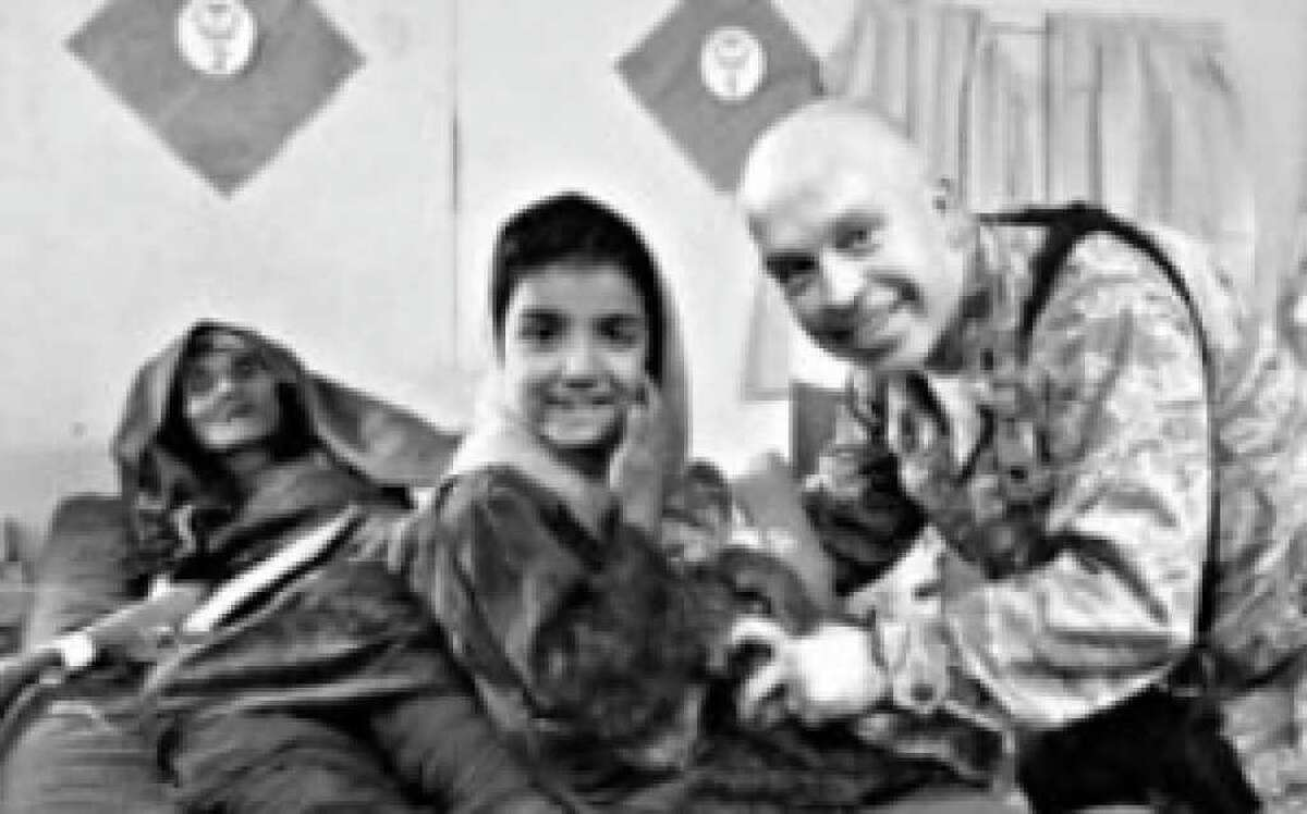 """Air Force Maj. Tobin Griffeth of San Antonio visits with an Afghan girl who was at a hospital with her grandmother, her only living relative. He said the teddy bear and blanket he gave her left her """"thrilled she had a toy and a means to sleep a little warmer at night."""""""