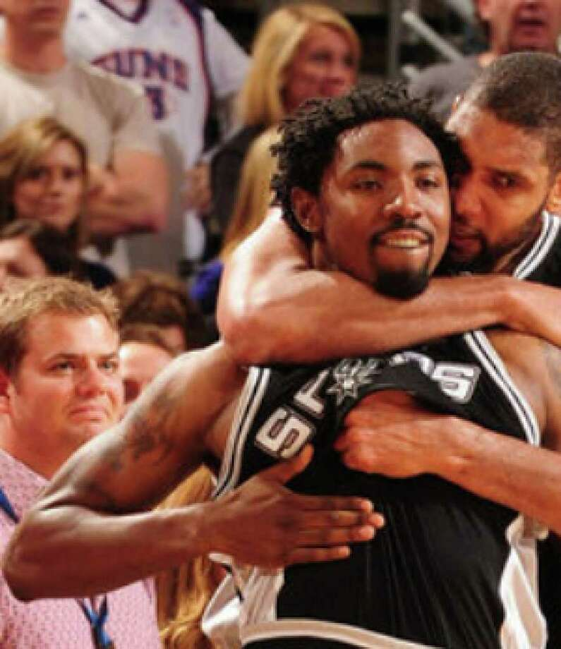 Tim Duncan (back) celebrates with Roger Mason Jr. last Christmas after Mason hit a 3-pointer at the buzzer to beat the Suns.