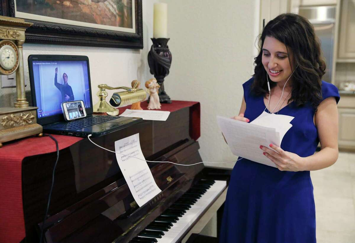 """San Antonio Symphony Mastersingers member Lindsey Vande Hey rehearses as a video of Sebastian Lang-Lessing, music director emeritus of the symphony plays. Most members of the 120-voice choir are working with the symphony in what will be an online performance of the last five minutes of Gustav Mahler's Symphony No. 2, """"Resurrection."""""""