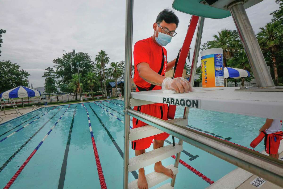 Piero De la Torre, pool manager at the D. Bradley McWilliams YMCA at Cypress Creek disinfests the lifeguard station Monday, June 1, 2020, in Houston.