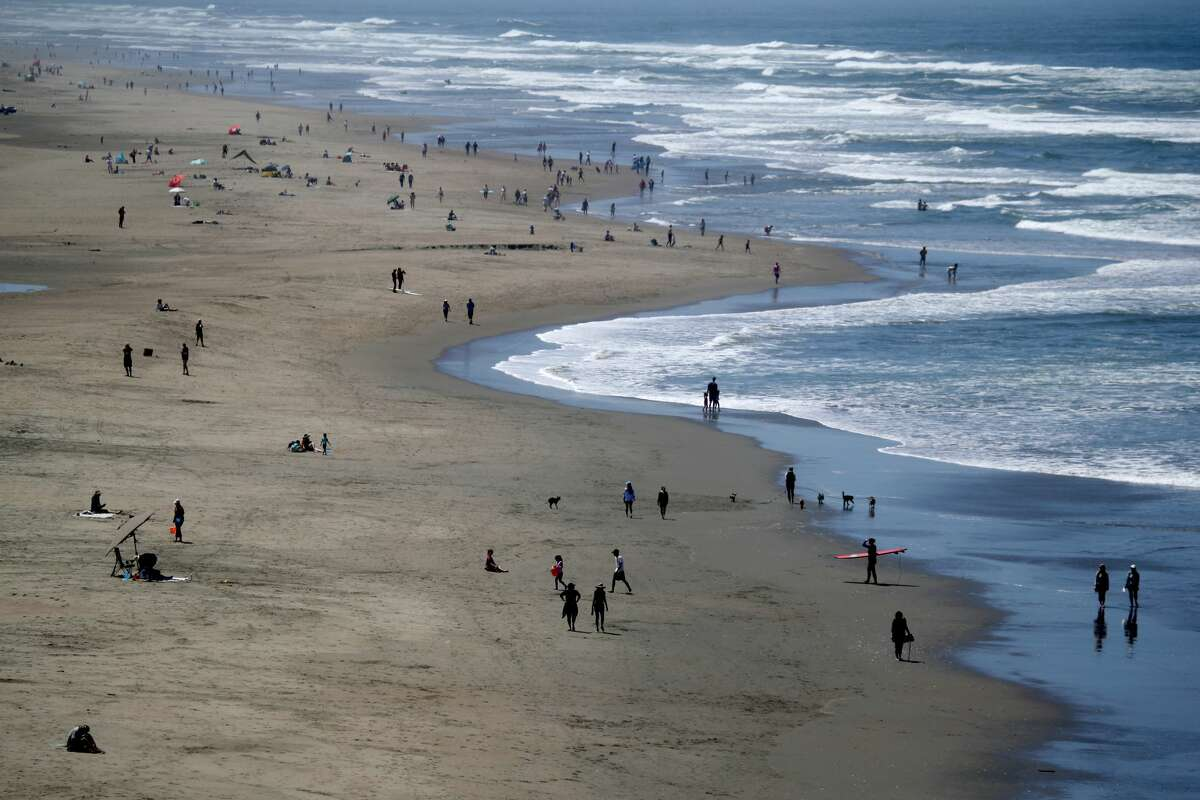 FILE - People walk along Ocean Beach on May 26, 2020 in San Francisco, California. The beach's parking lots were closed for the remainder of the weekend after over a thousand people were seen gathering there to celebrate Burning Man on Saturday.