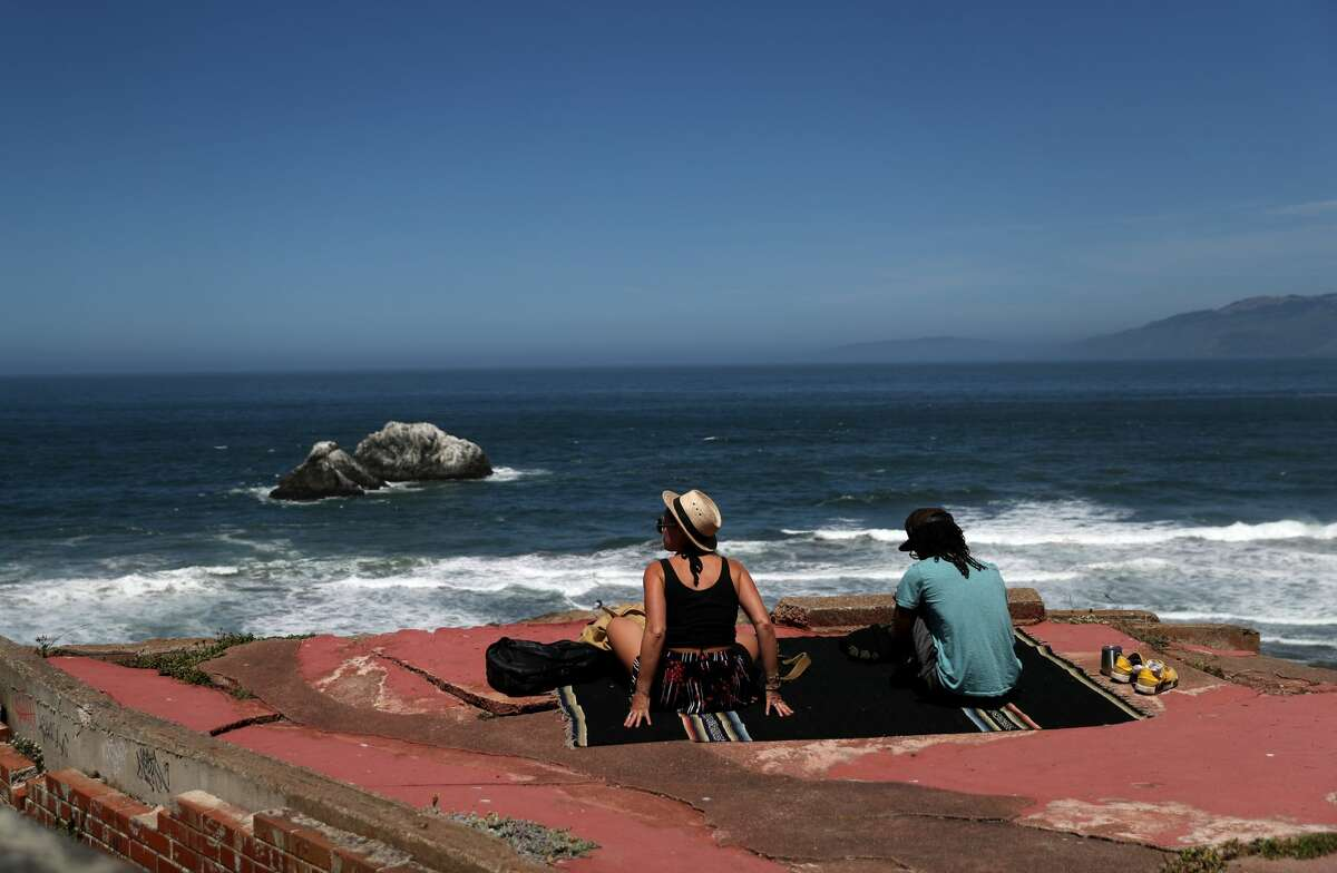A couple sits on a rock overlooking Ocean Beach on May 26, 2020 in San Francisco, California.