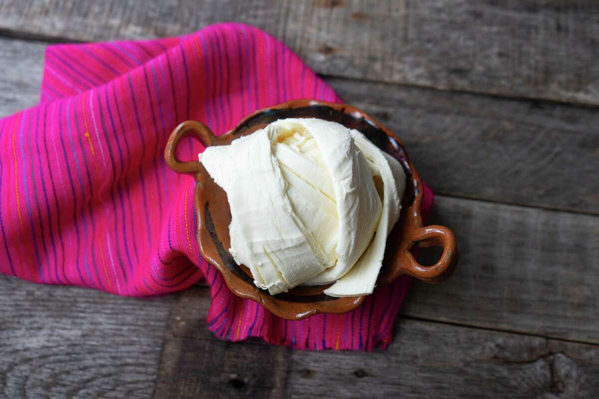 Fresh Oaxaca cheese in clay pot on old wood background