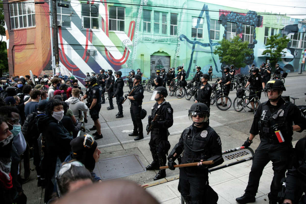 Seattle Police stand guard outside a precinct as people protest the death of George Floyd, in the Capitol Hill neighborhood of Seattle, Washington on June 1, 2020. - Major US cities -- convulsed by protests, clashes with police and looting since the death in Minneapolis police custody of George Floyd a week ago -- braced Monday for another night of unrest. More than 40 cities have imposed curfews after consecutive nights of tension that included looting and the trashing of parked cars. (Photo by Jason Redmond / AFP) (Photo by JASON REDMOND/AFP via Getty Images)