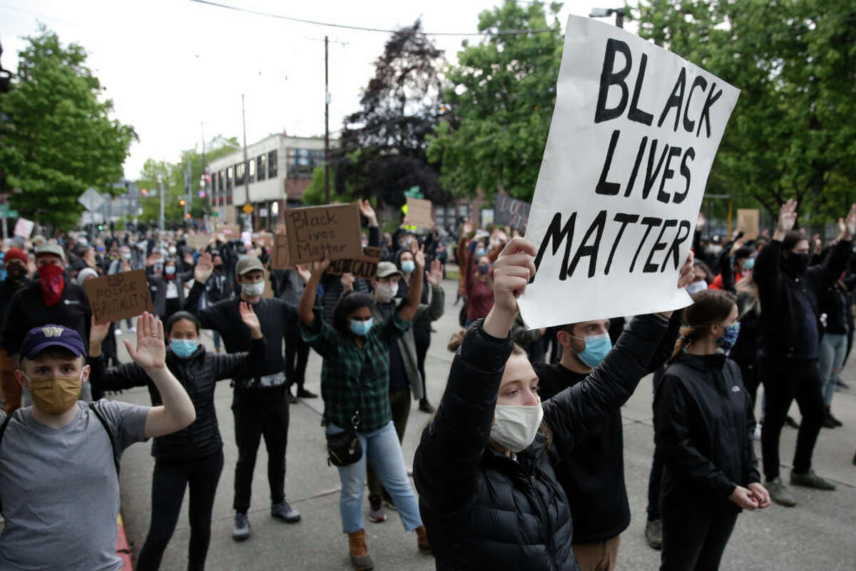 People hold up placards to protest over the death of George Floyd, an unarmed African-American man who died in police custody in Minneapolis on May 25, outside the Seattle Police Department's East Precinct in Seattle, Washington on June 2, 2020. - Protesters defied curfews across the United States on June 2 as leaders scrambled to stem anger over police racism while President Donald Trump rejected criticism over his use of force to break up a peaceful rally. (Photo by Jason Redmond / AFP) (Photo by JASON REDMOND/AFP via Getty Images)
