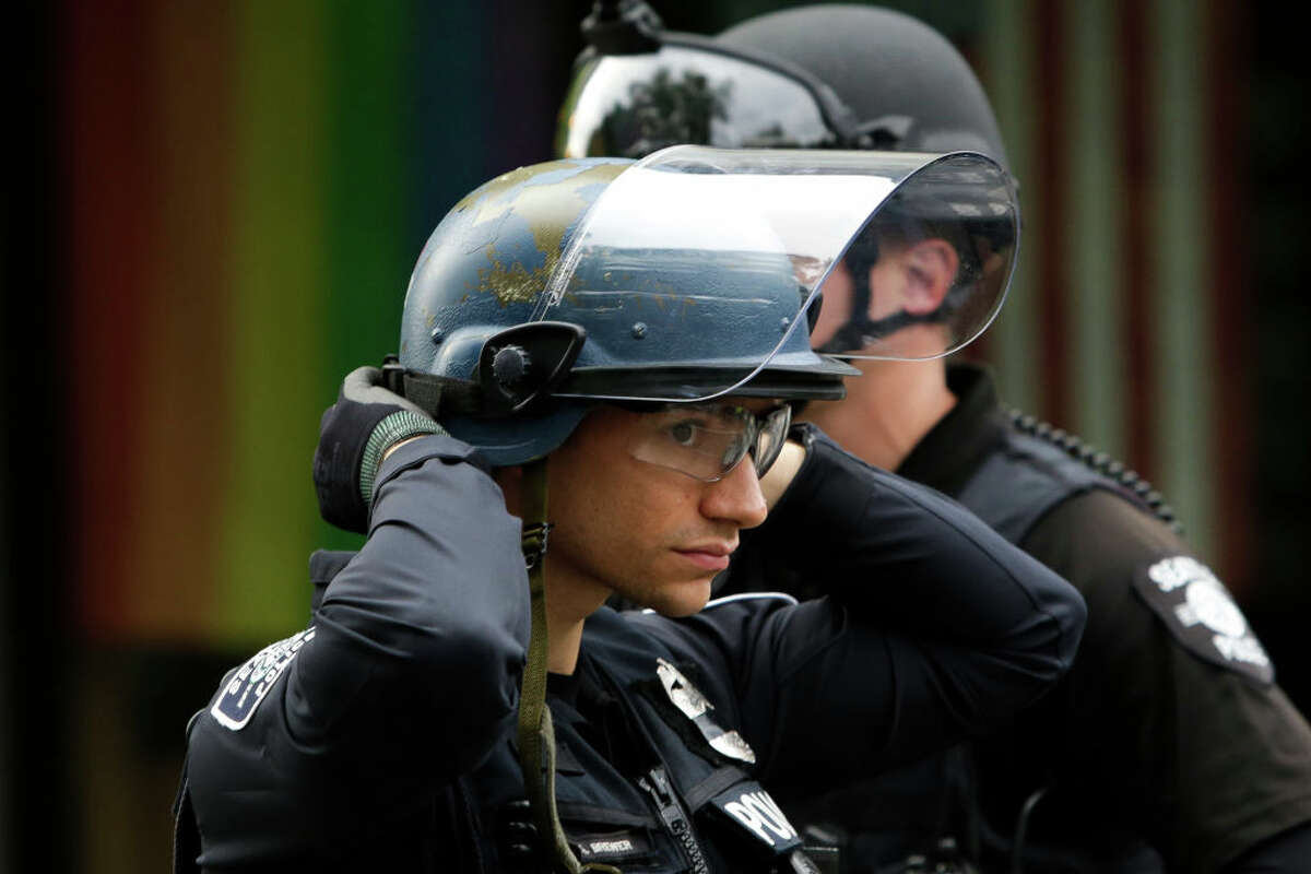 A police officer adjusts his helmet at a barricade as people protest nearby over the death of George Floyd, an unarmed African-American man who died in police custody in Minneapolis on May 25, outside the Seattle Police Department's East Precinct in Seattle, Washington on June 2, 2020. - Protesters defied curfews across the United States on June 2 as leaders scrambled to stem anger over police racism while President Donald Trump rejected criticism over his use of force to break up a peaceful rally. (Photo by Jason Redmond / AFP) (Photo by JASON REDMOND/AFP via Getty Images)
