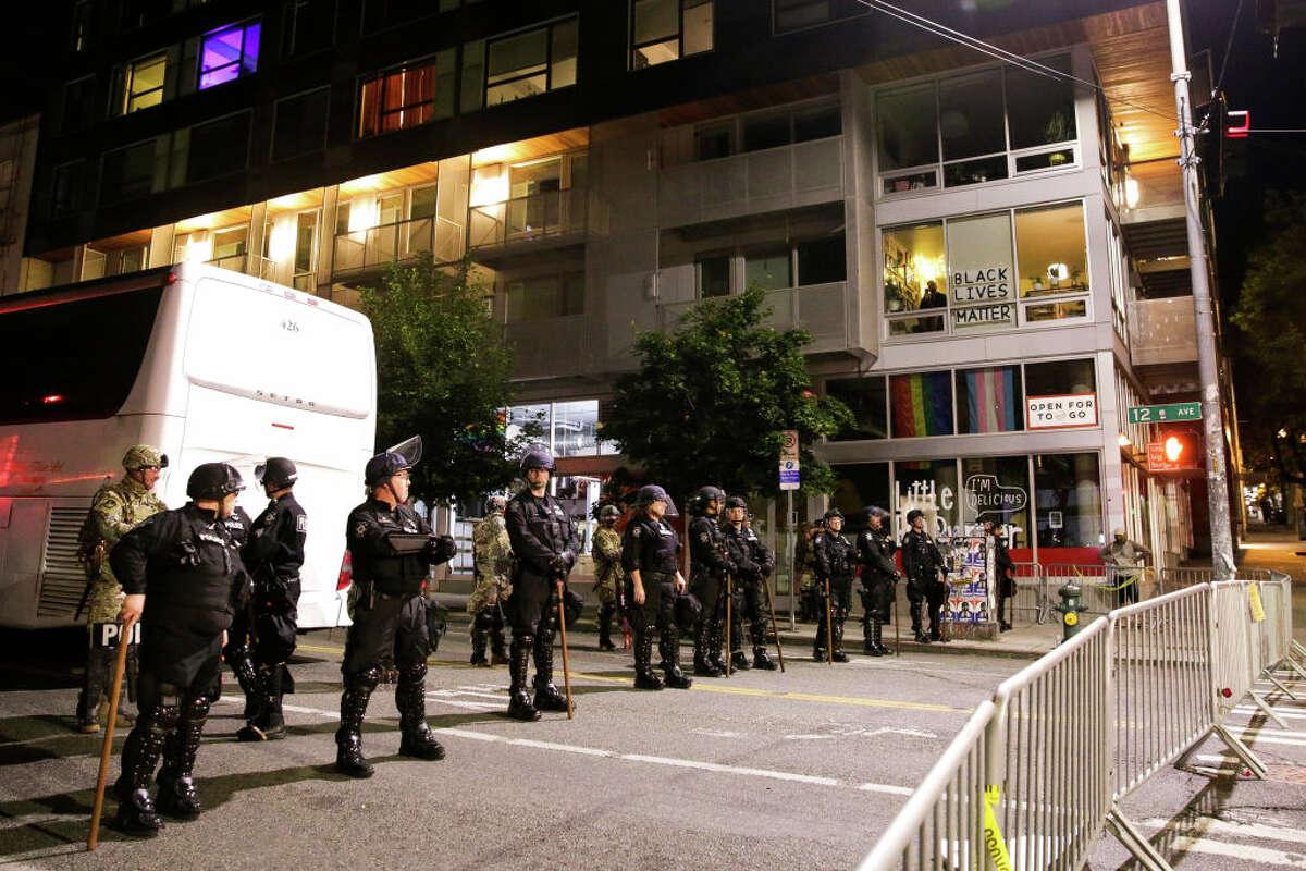 Police stand at a barricade as people protest nearby over the death of George Floyd, an unarmed African-American man who died in police custody in Minneapolis on May 25, outside the Seattle Police Department's East Precinct in Seattle, Washington on June 2, 2020. - Protesters defied curfews across the United States on June 2 as leaders scrambled to stem anger over police racism while President Donald Trump rejected criticism over his use of force to break up a peaceful rally. (Photo by Jason Redmond / AFP) (Photo by JASON REDMOND/AFP via Getty Images)