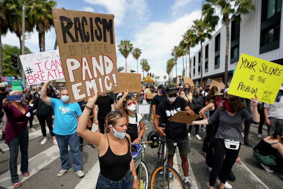 Demonstrators hold up signs Tuesday, June 2, 2020, in the Venice Beach area of Los Angeles during a protest over the death of George Floyd. Floyd died in police custody on May 25 in Minneapolis. (AP Photo/Ashley Landis) / Copyright 2020 The Associated Press. All rights reserved
